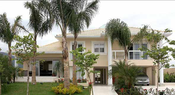 Casa com fachada na cor palha com toques de branco Foto de The Holk