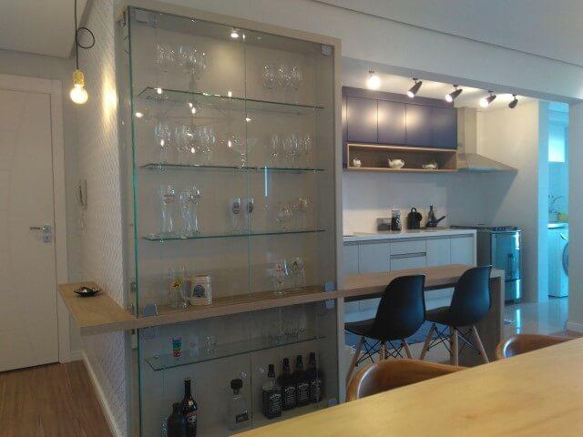 Cozinha americana com cristaleira moderna de vidro com taças e copos Projeto de Vanessa Lora