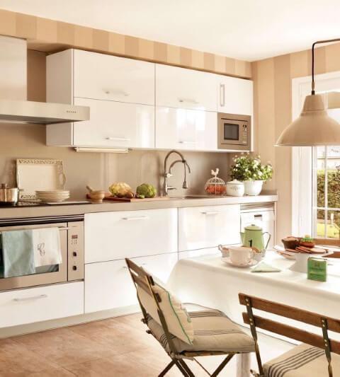 Cozinha com paredes em cor de palha e armários brancos Foto de El Mueble
