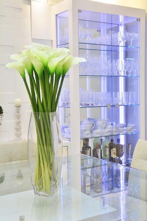 Cristaleira moderna de vidro com estrutura branca em sala com decoração clara Projeto de Graça Brenner