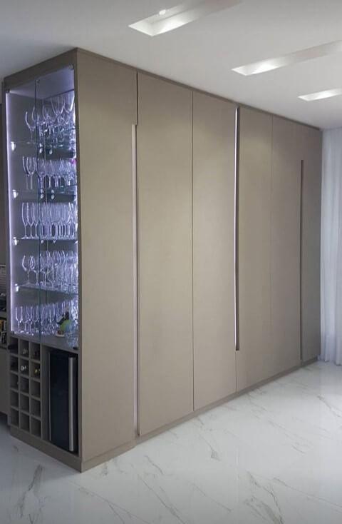Cristaleira moderna iluminada embutida em armário com adega embaixo Projeto de Mauren Buest