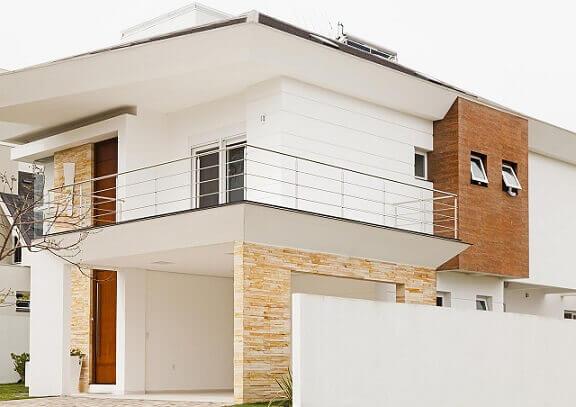 Fachada de casa duplex branca com pedras e tijolinhos Projeto de Marcos Biazus