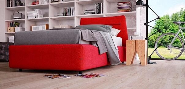 Piso vinílico claro em quarto de solteiro com cama vermelha Foto de Duratex Madeira
