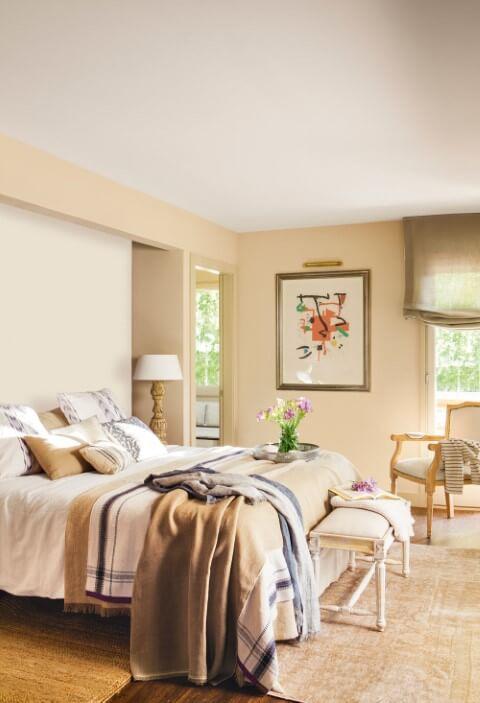 Quarto de casal com parede cor palha com roupa de cama marrom, branco e azul Foto de GD Home