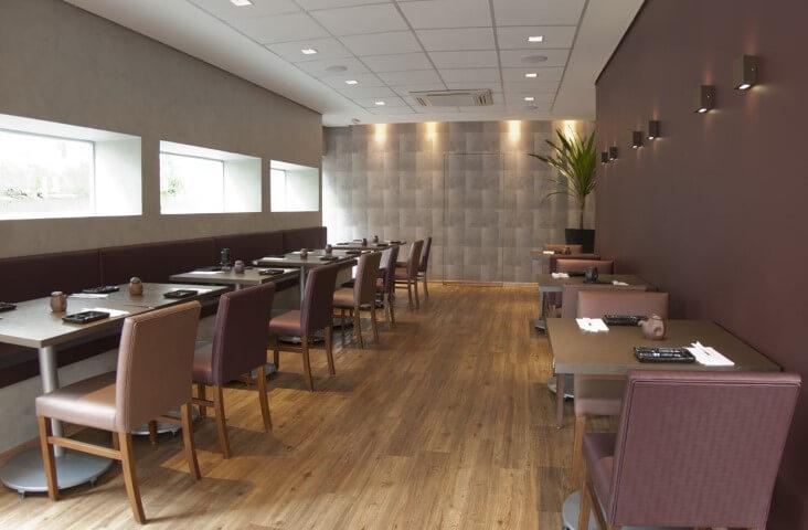 Restaurante com piso vinílico que imita madeira e móveis em tons amadeirados Projeto de Monica Spada Durante
