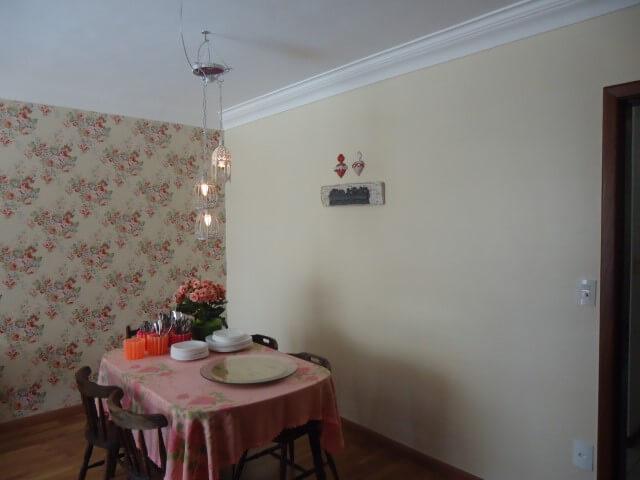 Sala com parede com papel de parede florida e parede cor palha Foto de DiMercandelli Studio