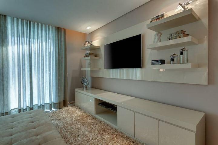 Sala de TV com parede cor palha e móveis planejados em tom claro de bege Foto de Isabella Magalhães Arquitetura & Interiores