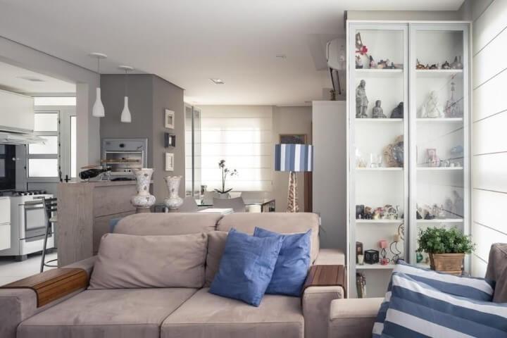 Sala de estar com cristaleira moderna branca com objetos de decoração dentro Projeto de Braccini Lima