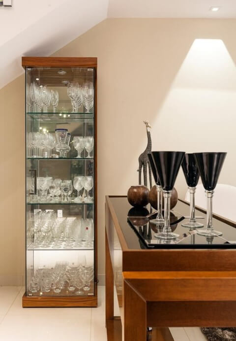 Sala de estar com cristaleira moderna de madeira com porta e prateleiras de vidro Projeto de Laura Santos