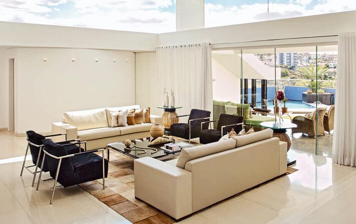 Sala de estar com parede cor palha e poltronas pretas Foto de Modernidade Móveis
