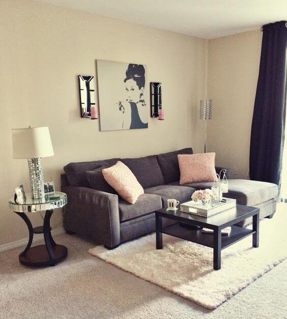 Sala de estar com parede cor palha, sofá cinza e toques cor de rosa Foto de Viver em Casa