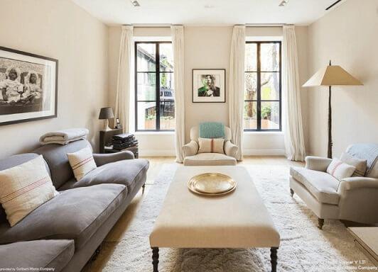 Sala de estar com paredes cinza palha e sofá cinza Foto de Gotham Photo Company