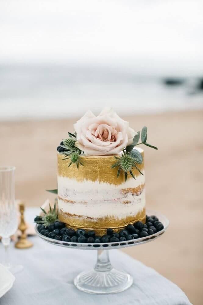 bolo de casamento simples decorado com detalhes em dourado e grande rosa no topo Foto Cake Couture NI