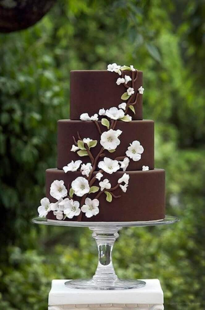bolo de casamento simples e bonito todo de chocolate com flores brancas Foto Weddbook