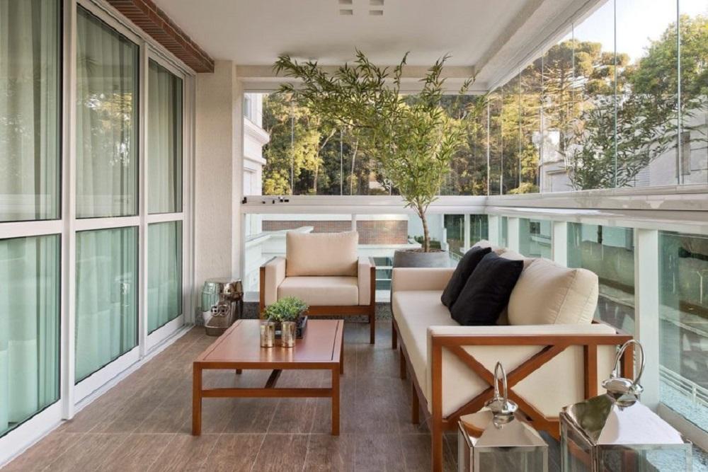 decoração clean com sofá e mesa para sacada com cortina de vidro Foto Assetproject