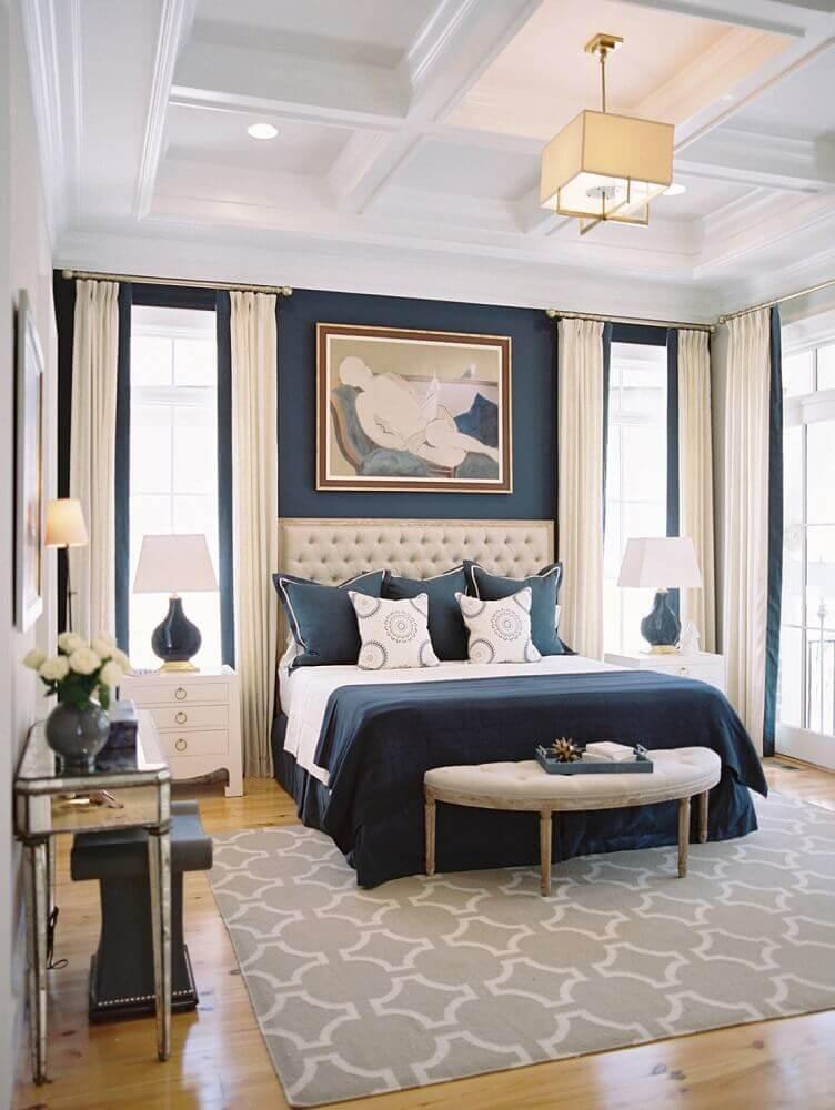 decoração com estilo clássico com tapete para quarto de casal com parede azul marinho e cabeceira capitonê Foto Buyer Select