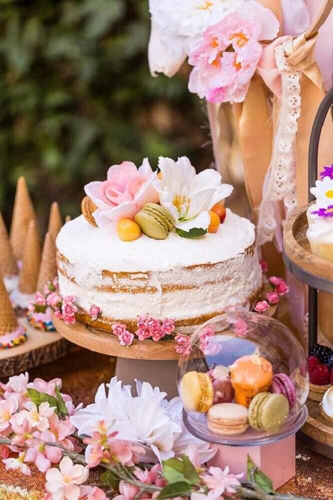 decoração romântica com bolo de casamento simples com chantilly e flores Foto Brit + Co
