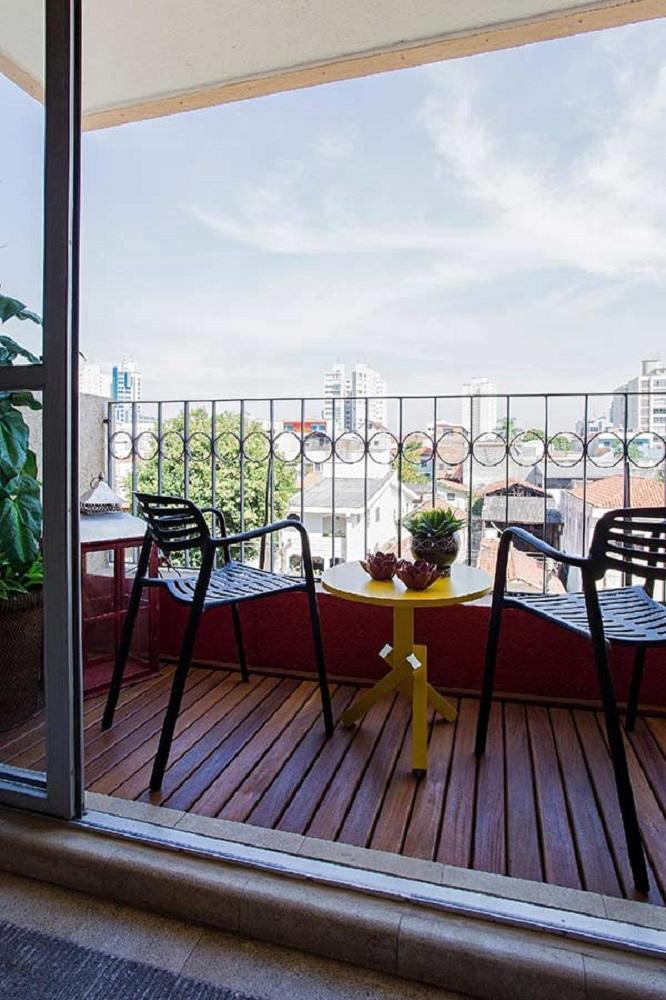 mesa amarela para sacada com piso de madeira Foto The Holk