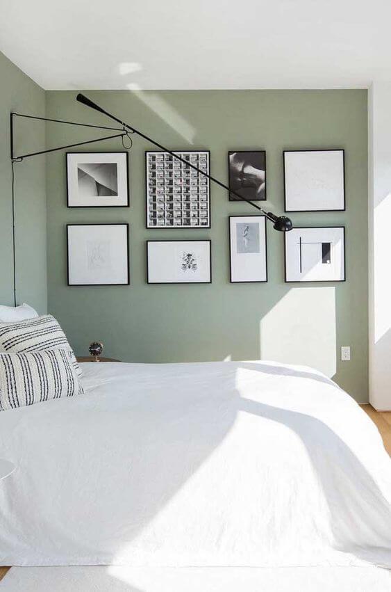 Quarto verde com conjunto de molduras para quadros em preto e branco