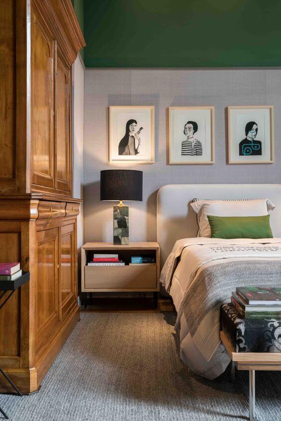 Quarto verde com molduras para quadros