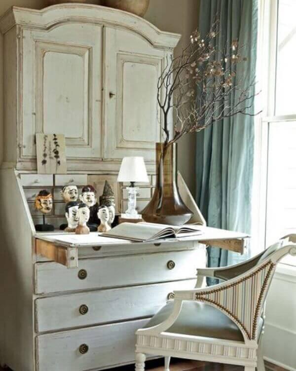 A pátina branca da escrivaninha valoriza o móvel