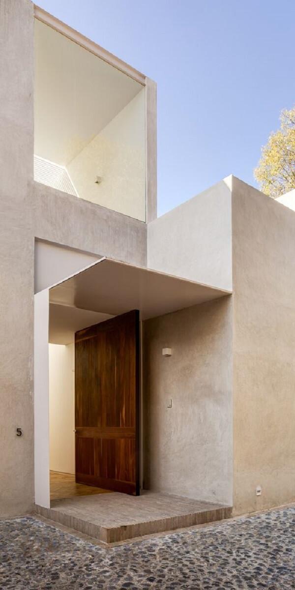 A porta pivotante de madeira se destaca nessa fachada de concreto