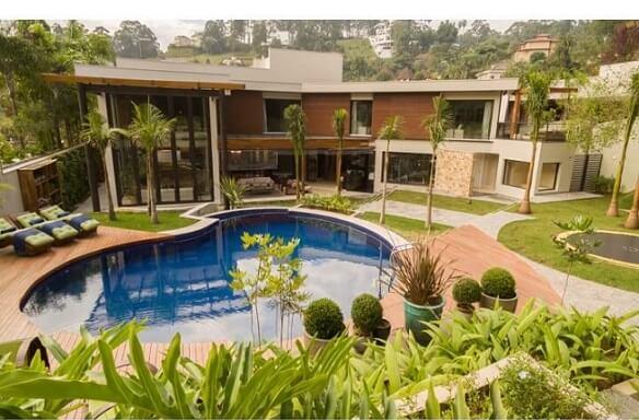 Casa ampla com jardim com piscina com deck de madeira Projeto de C2H Arquitetos