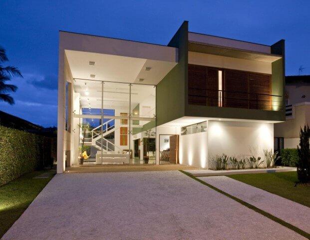 Casa duplex com parede de vidro e fachada branca e verde Projeto de FC Studio