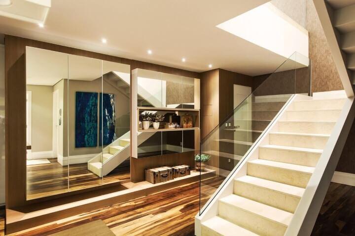 Casa duplex com vidro transparente na escada e parede espelhada Projeto de Juliana Pippi
