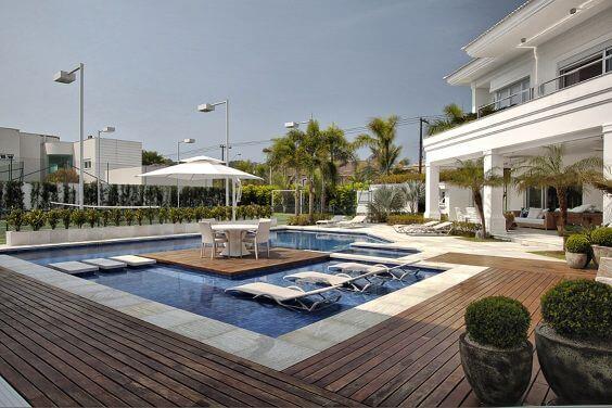 Casa grande com piscina com deck de madeira e centro de madeira com mesa e cadeiras Projeto de Bianka Mugnatto