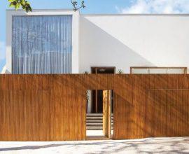 Casa moderna com portão de madeira e porta do mesmo material Projeto de Francisco Calio