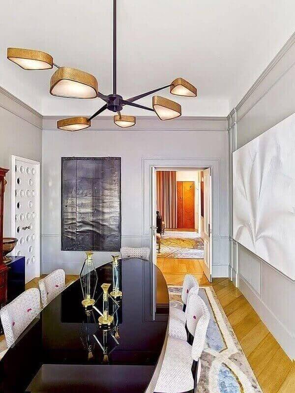 a sala de jantar tem lustre com detalhes em dourado e design arrojado