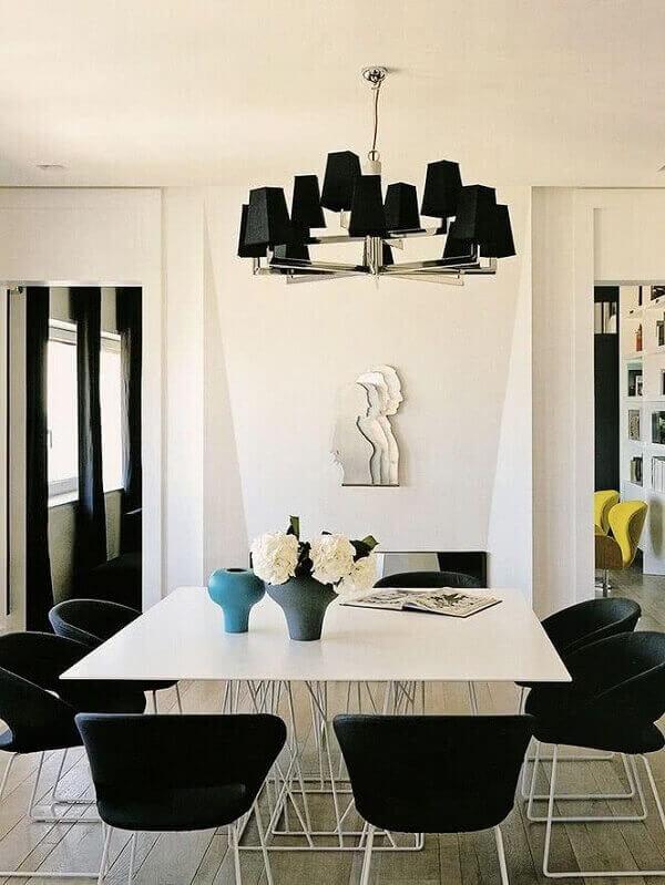 lustres com spots pretos complementam a decoração da sala de jantar