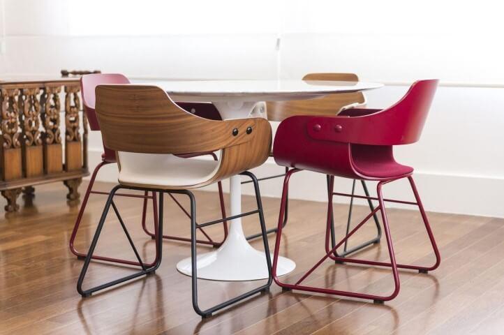 Mesa branca com móveis de madeira e coloridos na sala de jantar Projeto de Carla Cuono