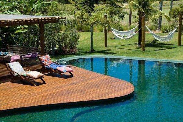 O deck de madeira acompanha o formato da piscina