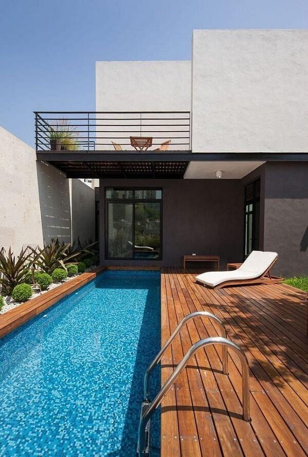 O deck segue o formato da piscina estreita e comprida