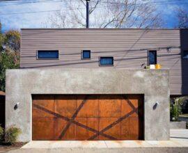 O portão de madeira se conecta perfeitamente com a fachada de concreto da casa