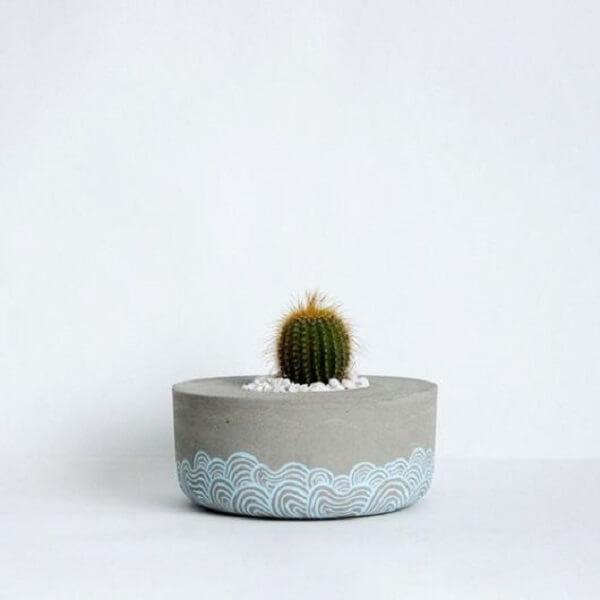 O vaso de cimento redondo tem traços em tons de azul