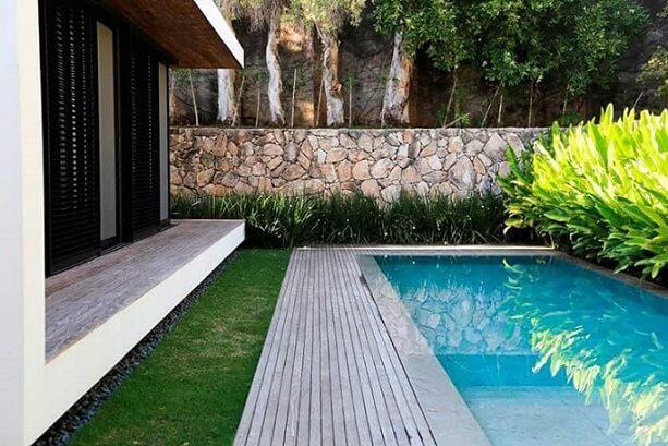 Piscina com deck ao lado da casa Projeto de Daniel Nunes Paisagismo
