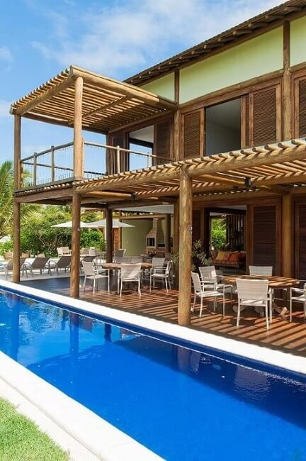 Piscina com deck coberto com gazebo e mesas Projeto de SQ+ Arquitetos