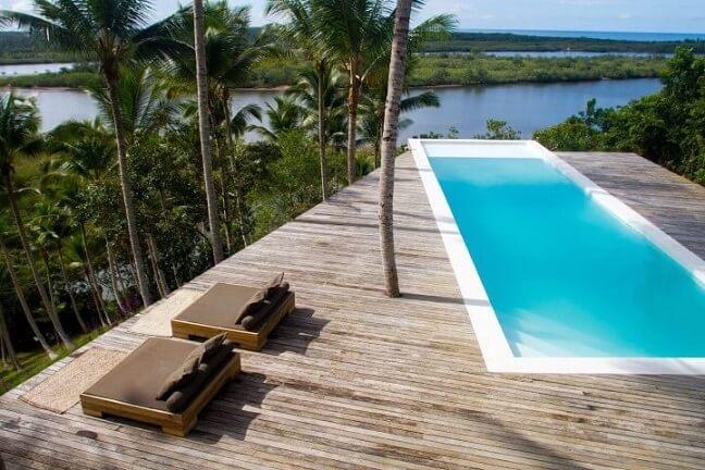 Piscina com deck de madeira clara e vista ampla Projeto de Meireles Pavan Arquitetura