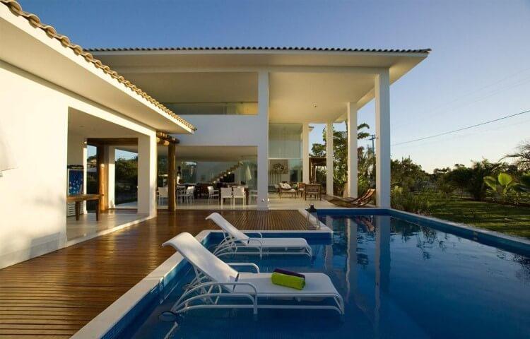Piscina com deck de madeira em casa grande e moderna Projeto de SQ+ Arquitetos