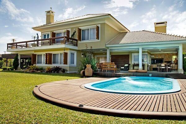 O deck de madeira segue a curvatura da piscina