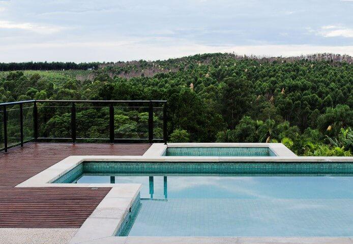 Piscina com deck e piscina pequena ao lado Projeto de Flavia Medina