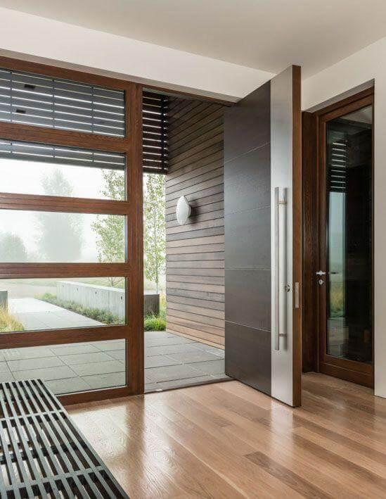 Porta pivotante de madeira com detalhe prateado Foto de Carney Logan Burke Architects