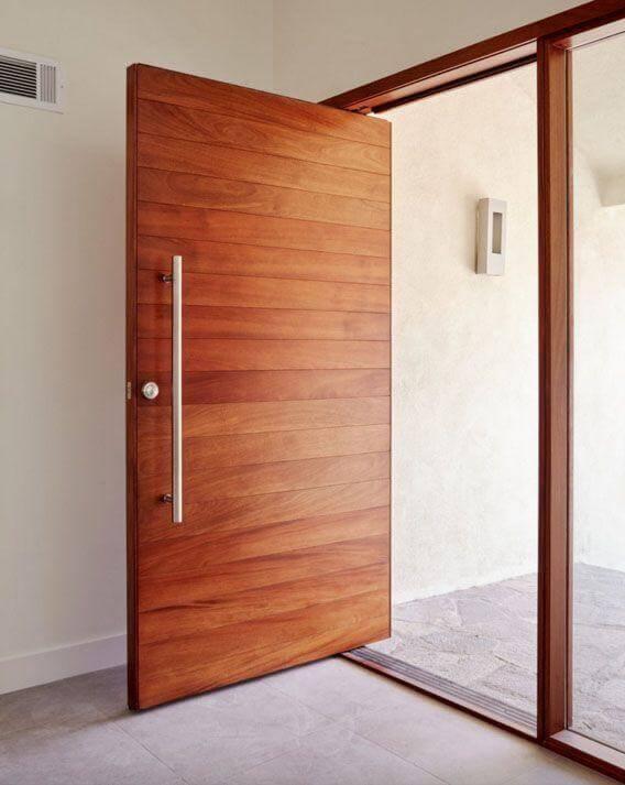Porta pivotante de madeira com puxador de inox Foto de Pivot Door Company