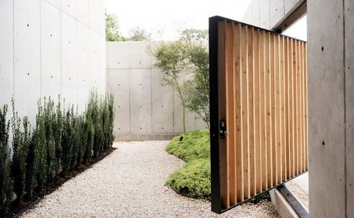 Porta pivotante de madeira e ferro no muro Foto de Robertson Design