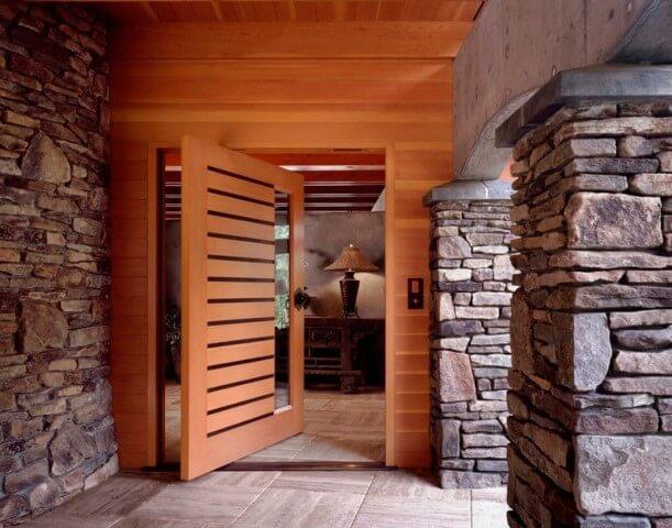 Porta pivotante de madeira em fachada com pedras Foto de Casa do Portal