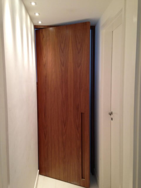 Porta pivotante de madeira estreita na entrada do apartamento Projeto de Iago Patucci
