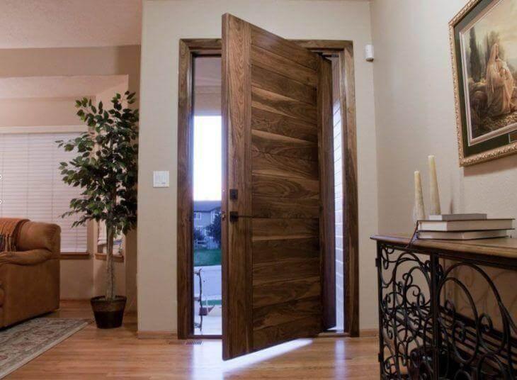 Porta pivotante de madeira na entrada da casa Foto de Pivot Door Company